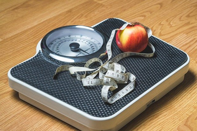 Photo of a scale, tape measure, and an apple.