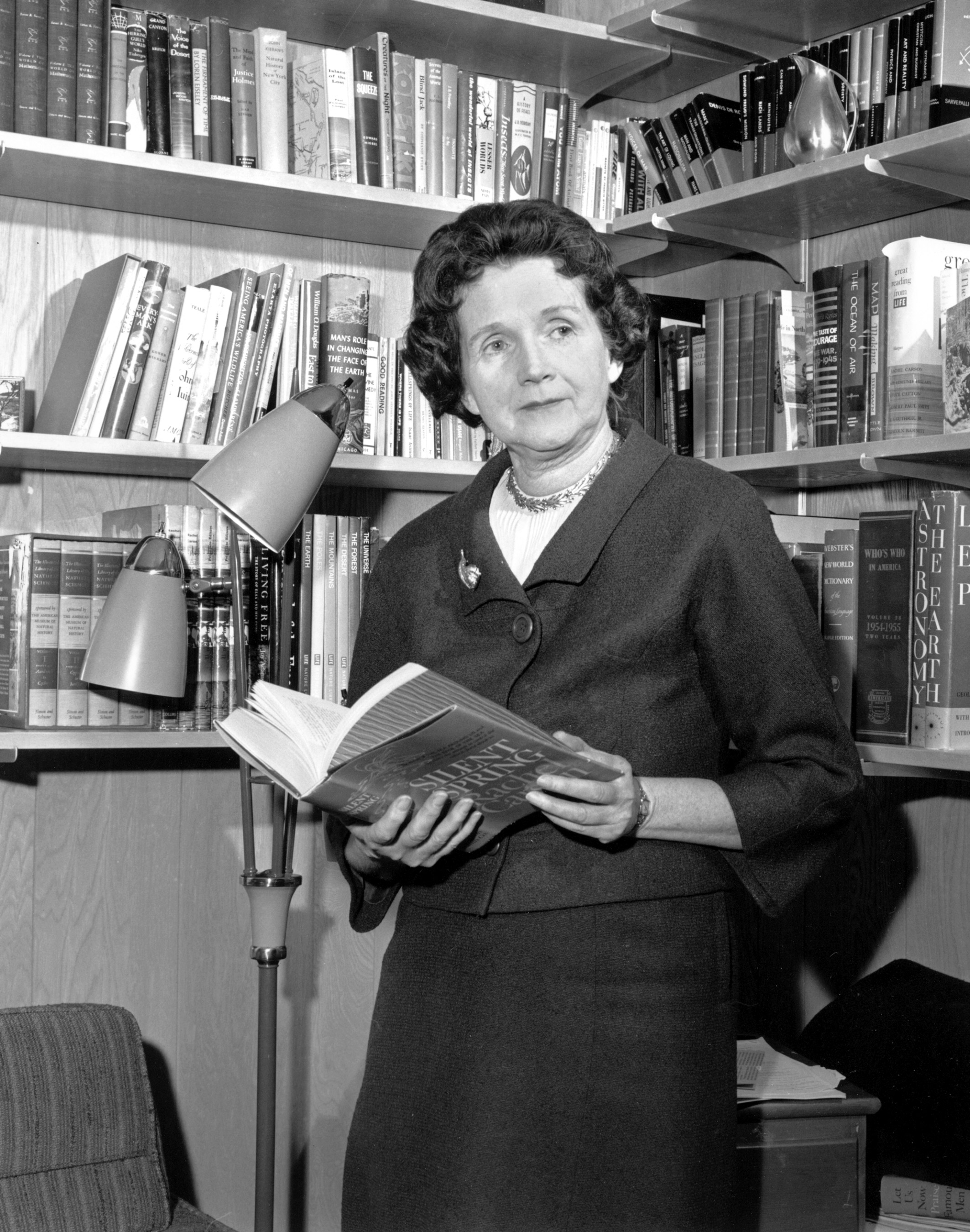 Image of Carson standing with Silent Spring in her hands