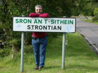 Photo of a man at a city sign which lists two different spellings for a town