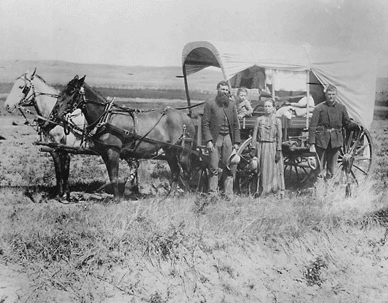 A family poses with the wagon in which they live and travel daily during their pursuit of a homestead