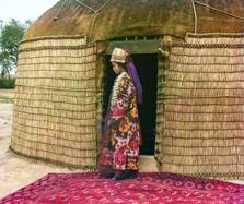 Turkman woman standing at the entry to a grass and hide covered yurt. Collection of the Library of Congress Prints and Images File